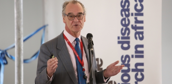 Image of Robert J Willkinson speaking with banner reading Wellcome Centre for Infectious Diseases Research in Africa in the background.